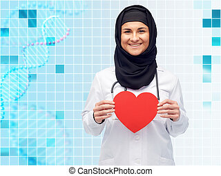 muslim female doctor in hijab holding red heart