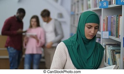 Muslim female student reading a book in library - Serious...