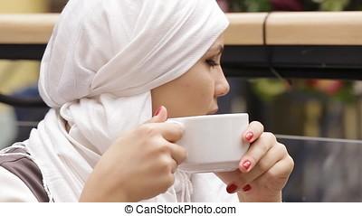 Muslim Girl Drinking Tea In Cafe