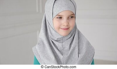 Muslim girl in grey hijab is looking in camera and laughing....