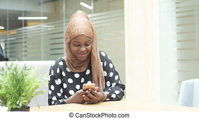 Muslim girl in hijab uses smartphone for online shopping. -...