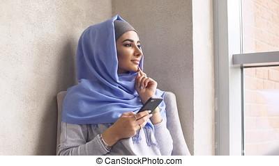 Muslim girl is holding a modern mobile phone. Beautiful...
