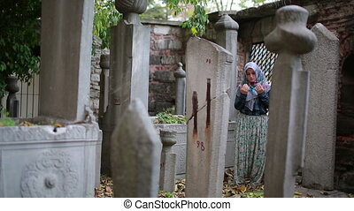 Muslim girl praying in small graveyard