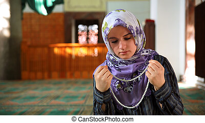 Muslim girl saying her everyday salat prayer in mosque