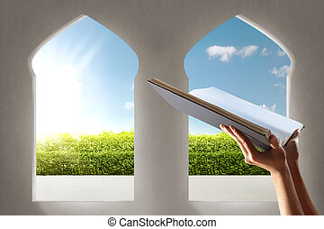 Muslim hands holding quran open in the mosque with garden view from window arches