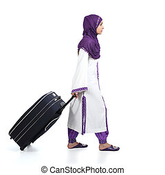 Muslim immigrant woman wearing a hijab walking carrying a suitcase