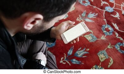 Muslim is reading Quran with mobile phone in a mosque -...