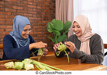 muslim making traditional ketupat or rice cake - muslim...