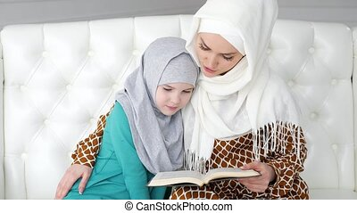 Muslim mom in hijab is reading her little daughter a book...
