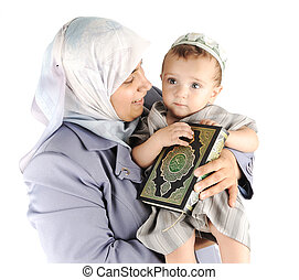 Muslim mother and her little son holding a Koran