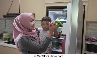 muslim mother carrying her son and open the fridge looking for sweets treat