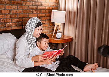 muslim mother reading a book with her son