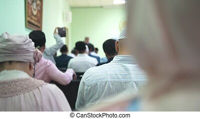 Muslim people sitting on armchairs at the islamic mass...
