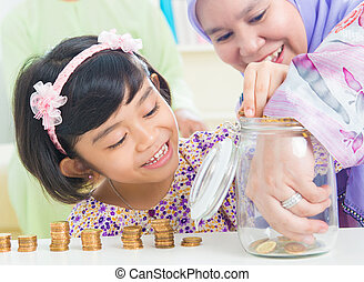 Muslim saving money concept - Muslim mother and daughter...