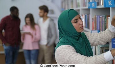 Muslim student searching for a book in library - Muslim...
