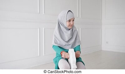 Muslim teen girl in hijab and dress is playing riding on toy...