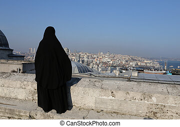 Muslim veiled woman watching the cityscape of Istanbul