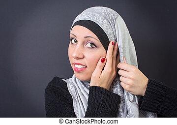 Muslim woman adjusting her headscarf - Beautiful muslim...