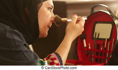 Muslim woman applying  make up