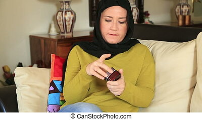 Muslim woman applying some lotion