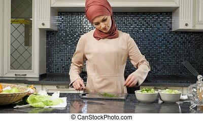 Muslim woman cooks lunch for family cutting greens closeup...