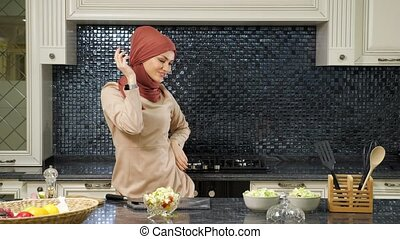 Muslim woman dances oriental dance after cooking dishes - ...