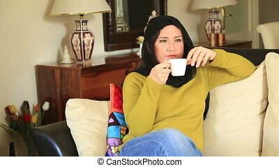 Muslim woman drinking coffee - Muslim woman relaxing indoor...