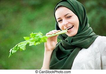 Muslim Woman Eating a Celery