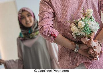 muslim woman having a flower from man