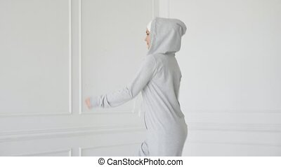 Muslim woman in hijab and fitness dress is making fitness...