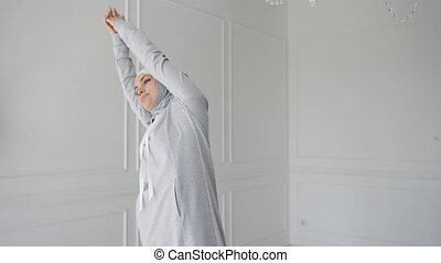 Muslim woman in hijab and fitness dress is making stretching...