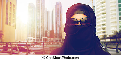 muslim woman in hijab and sunglasses at dubai city -...
