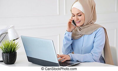 Muslim woman in hijab is talking mobile phone and typing on laptop at office work.