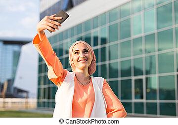 Muslim woman in hijab making selfie outdoors