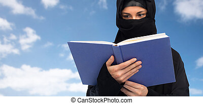 muslim woman in hijab reading book over sky - religion,...