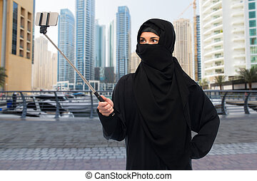 muslim woman in hijab taking selfie by smartphone -...