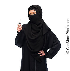 muslim woman in hijab with car key over white