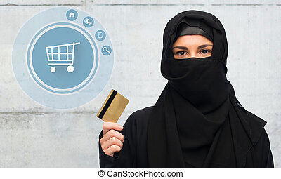 muslim woman in hijab with credit card over white