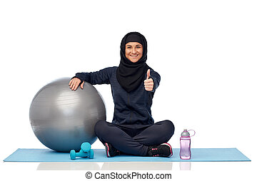 muslim woman in hijab with fitness ball and bottle