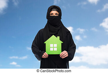 muslim woman in hijab with green house over white - ecology...