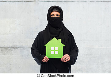 muslim woman in hijab with green house over white