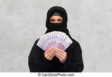 muslim woman in hijab with money over white