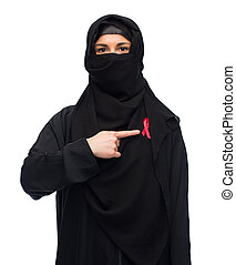 muslim woman in hijab with red awareness ribbon