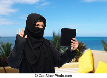 muslim woman in hijab with tablet pc having chat -...