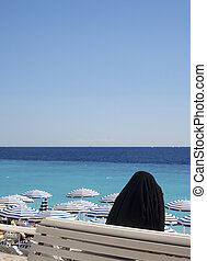Muslim woman in religious shround hijab overlooking beach  Promenade d' Anglais French Riviera Nice France