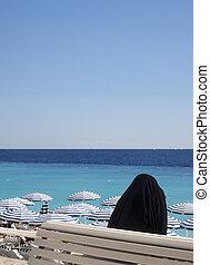Muslim woman in religious shround hijab overlooking beach...