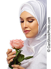 Muslim woman in white dress with rose