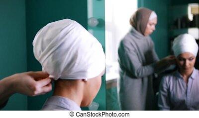 Muslim woman near mirror tying Islamic turban for attractive...