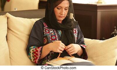Muslim woman praying and reading koran