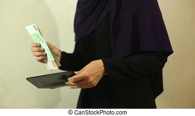 Muslim woman puts money in an envelope - Muslim woman in a...